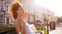 Beautiful girl smiling enjoying relaxing sitting on bench outside Slow motion Stock Footage