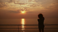 Beautiful female phorograph taking picture of sunrise at sea Slow motion Stock Footage
