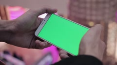 Male hands using smartphone with green screen in shopping mall. Lot of people at Stock Footage