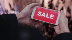 Hand holds smartphone, discounts on screen. Mall black friday, sales. Lots of Stock Footage