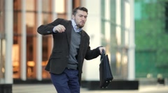 Attractive man with a beard and briefcase dancing in the street Stock Footage