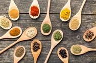 Various spices in wooden spoons. Stock Photos