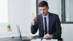 Young businessman hitting upon a good idea and writing on a paper Stock Footage