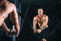 Bodybuider demonstrate crossover exercises in the gym Stock Photos