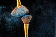 Two brushes and blue scattered shadows at black background Stock Photos