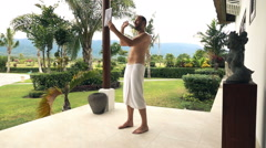 Happy man in towel chatting on tablet on patio in garden, super slow motion Stock Footage