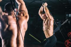 Man exercising in trainer for triceps muscles in the gym Stock Photos