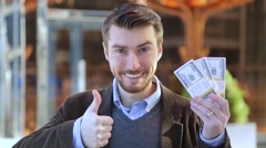 Happy man holding in his hand bundles of money dollars and showing thumbs up Stock Footage