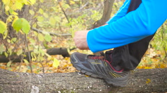 Man runner tying her shoes on a fallen tree in the autumn forest. Stock Footage