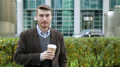 Attractive man drinking coffee or tea from paper cup, looking at camera, smiling Stock Footage