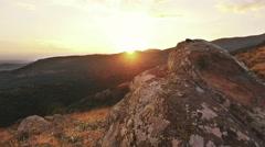 Hiker moving pov amoung rocky mountain scenery toward sunset Stock Footage