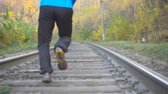 Man Jogging Train Tracks Railway in Autumn Season in forest. Training and exe Stock Footage