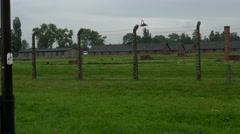 Buildings of Auschwitz concentration camp in Poland behind barbed wire fence Stock Footage