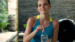 Portrait of happy, sporty woman resting after workout at home, super slow motion Stock Footage