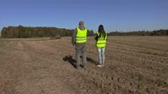 Farmers couple walking away on unplowed field Stock Footage