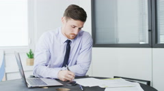 Young businessman signs a document and thinks deeply about something Stock Footage