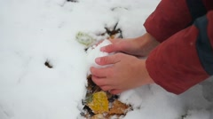 Child sculpts a snowball bare hands Stock Footage