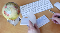 Top shot of bsiness man writing a cheque with globe spinning Stock Footage