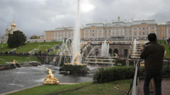 Man taking photos of the Grand palace fountains in Peterhof St.Petersburg, Russi Stock Footage