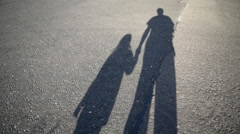 Shadow of parent and child walking along road Stock Footage