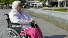 Old woman in a wheelchair is resting in a city near a fountain Stock Footage