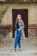 Beautiful stylish young woman in a warm scarf blue jeans trendy shoes Stock Photos