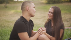 Cute couple drinking white wine on a picnic smiling at each other on a sunny day Stock Footage