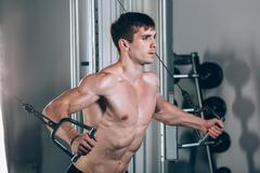 Handsome bodybuilder works out pushing up excercise in gym Stock Photos