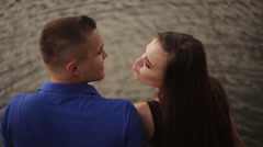Portrait of a happy beautiful young couple man and woman kissing outdoors on the Stock Footage
