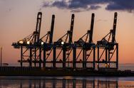 Sunset or Sunrise Behind Cranes at Container Port Stock Photos