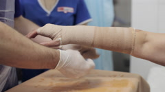 Doctor lay on gypsum on the hand female patient Stock Footage