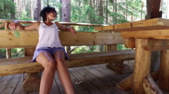 Happy young woman resting on bench on the balcony at wooden house in the coun Stock Footage