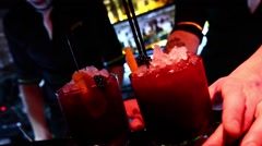 Two delicious purple caipirinha cocktails with blackberry gets handed Stock Footage