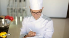 Male chef in a commercial kitchen sitting on the cheer and writing a reciepe Stock Footage