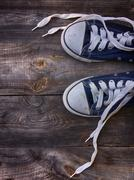 Old worn blue sneakers with white laces untied Stock Photos