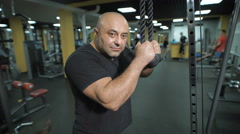 Close-up of a muscular man with strong arms in the fitness club Stock Footage