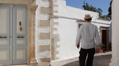 Man explores a narrow street in Chora on the island of Patmos Stock Footage