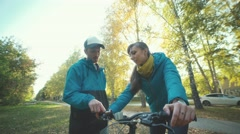 A young man wearing a cap showing a girl bike device Stock Footage