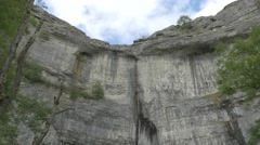 4K Huge Cliff Face of Malham Cove Lime Stone Rocks Trees Low Angle Stock Footage
