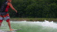 A man wake surfing behind a boat on a lake. Stock Footage