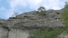 4K Trees on the Peak of Huge Cliff Face Malham Cove Lime Stone Rocks Stock Footage
