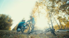 Pit stop on the bike trip in the autumn forest. Man repairing bicycle Stock Footage