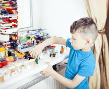 Little cute preschooler boy playing lego toys at home happy smiling, lifestyle Stock Photos