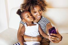 Adorable sweet young afro-american mother with cute little daughter, hanging at Kuvituskuvat