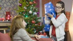 Little girl shaking a Christmas present in front of a Christmas tree Stock Footage