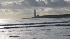 Waves and Scurdie Ness lighthouse near Montrose Scotland Stock Footage