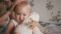 Young beautiful woman hugging her cute daughter with toy in berroom - motherhood Stock Footage