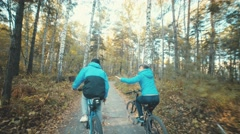 Man and woman riding bicycles and holding hands Stock Footage