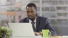 Businessman at his desk upset and looking at his watch Stock Footage