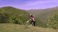 Girl mountainbiker pushing her bike uphill on a meadow Stock Footage